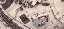 A Miniature Christmas Village. Miniature Of Winter Scene With Christmas Houses, People, Train Station, Trees, City's Transportation, Lamp Posts, Road, Street And Express Way. Aerial View.