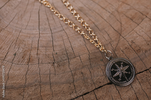 Slika na platnu Top view of compass pendant on an old brown cut wood