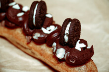 Eclair Decorated With Chocolate Cream And Cookies On Parchment Paper
