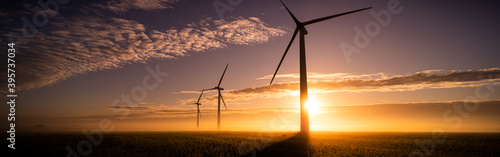 Fotografering Three commercial wind turbines in thick fog at sunrise in the English countrysid
