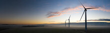 Aerial View Of Three Wind Turbines In The Early Morning Fog At Sunrise In The English Countryside Panoramic