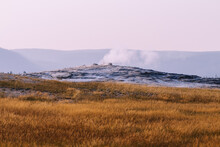 Steppe Covered With Yellow Grass And Steam Coming From Under The Surface In The Background