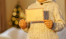 Child Is Posting A Letter For Santa Claus. Popular Children Christmas Activity. New Year Tree Blurred Bokeh Background. Not Recognizable Child.copy Space