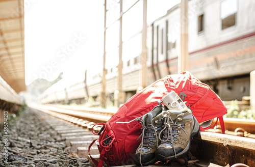 Obraz na plátně Map in backpack, camera, shoes and personal belongings in a train station with travelers