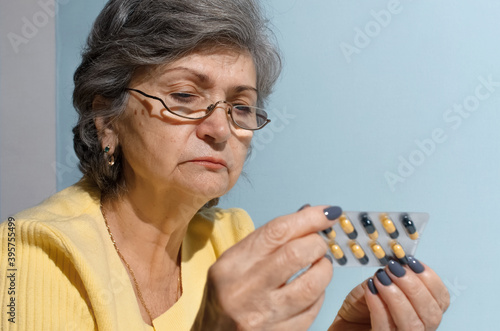 Fototapety, obrazy: Elderly woman with glasses trying to read instructions of the medicine pills, close-up. Treatment concept, sickness retirement