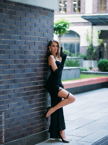 Beautiful young happy glamorous woman in a black evening dress with a gun in her hands. girl in elegant image of spy. High slit on leg. Retro fashion Model posing with pistol on street of modern city.