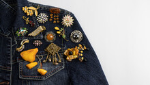 Beautiful  Rare Vintage Brooches With Amber, Sparkling Crystals And Pearls Are Pinned On The Dark Blue Denim Jacket.