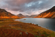 Dramatic View Of Wastwater Lake And Mountains With Golden Evening Light And Dark Clouds In Sky. Lake District, UK.