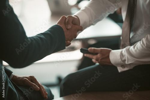Fototapeta Two businessmen handshaking colleagues or business partners on modern office background. Business concept. Close up shot. obraz na płótnie