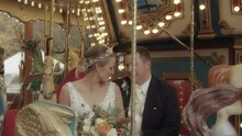 A Newlywed Couple Laugh, Kiss, And Pose On A Carousel