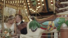 A Groom Kisses His Bride On The Forehead While Sitting On A Carousel