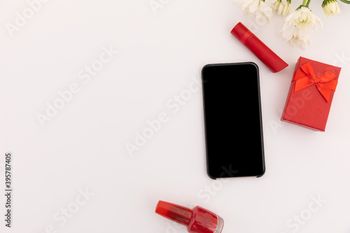 Smartphone, red lipstick, nail varnish, present and flowers on white background