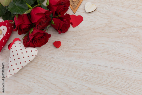 Fototapeta premium Bunch of red roses and hearts lying on wooden background