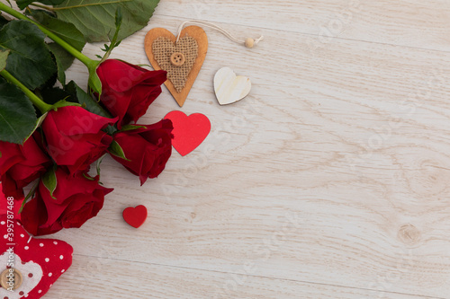 Obraz premium Bunch of red roses and hearts lying on wooden background