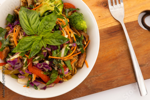 High angle view of bowl with salad and basil leaves on wooden board