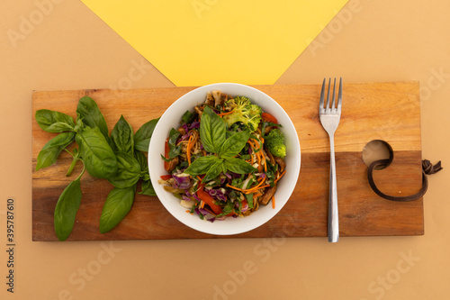 High angle view of bowl with salad and basil leaves on board