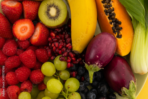 Close up of banana, berries, grapes and baby aubergines