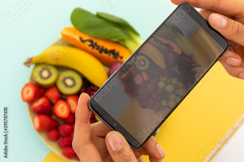Woman taking photos with smartphone of bowl of fruit