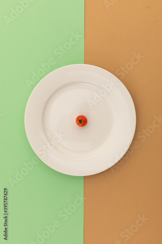 High angle view of cherry tomato on white plate on brown and green background