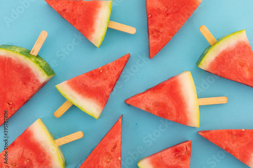 High angle view of multiple watermelon triangles on wooden sticks on blue background