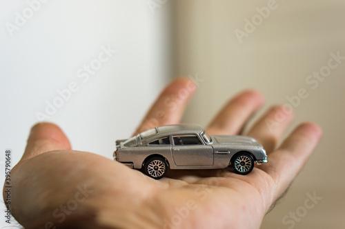 фотография POZNAN, POLAND - Mar 18, 2018: Aston Martin toy car on a hand