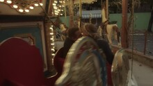 A Newlywed Couple Kissing Passing By On A Carousel