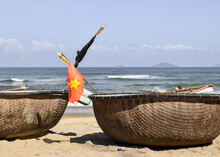 Close-up Of Basket Boats On The Sand In Front Of The Sea. There Is A Vietnam Flag In One Of Them. An Bang Beach, Hoi An, Vietnam.