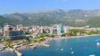 Aerial view of the picturesque coast of Budva in Montenegro with houses and beautiful nature with hills and trees on a sunny warm summer day. Port tourist city concept