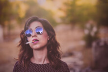 Portrait Of White Woman With Blue Sunglasses, Purple Polka Dot Dress And Cigar In Her Mouth With Ruins And Unfocused Trees Behind And Space For Text