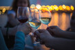 a party outside, celebrating and raising glasses with wine against blue night sky and yellow city lights, nice bokeh and lights reflections in the water