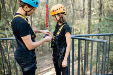 Rope Park Worker Wearing Safety Equipment On A Woman For A Bungee Jump