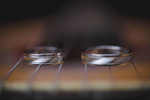 Closeup Of Silver Wedding Rings On Strings