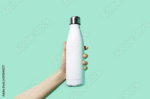 Fototapeta Close-up of female hand, holding white reusable steel stainless eco thermo water bottle on background of cyan, aqua menthe color. Be plastic free. Zero waste. obraz