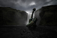 Statue Of Liberty Half Buried In The Sand Of A Huge Waterfall