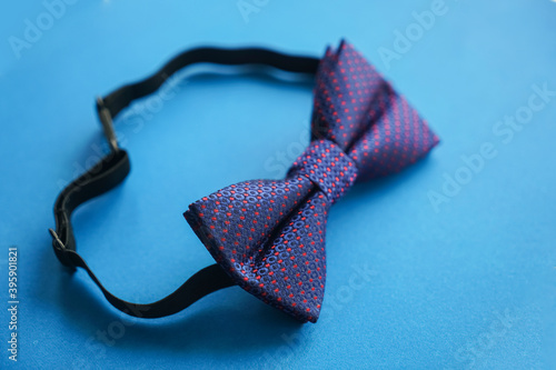 Tablou Canvas Elegant blue bow tie with violet pattern  isolated on blue paper background