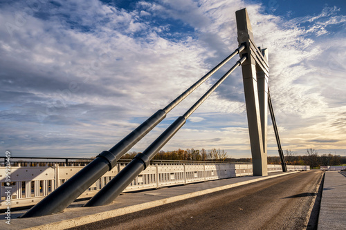 Fototapeta premium Moderne Stahlseilbrücke im Sonnenuntergang vor blauem Himmel