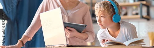Fotografia mom helping young son with laptop to do homework