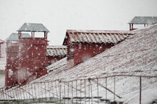 Brick Chimneys On Old City House Snow Covered Red Tiled Roof On Snowflakes And Gray Sky Background, Winter Snowfall In Europe, European Outdoor Winter Landscape