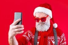 Modern Santa Claus Wearing Stylish Red Sweater, Hat And Scarf. Happy, Old Man With Mustache And Long White Beard Doing Selfie On Smartphone And Smiling. Winter Holidays, New Year Celebration Concept