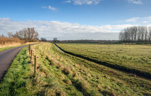 Characteristic Dutch Polder Landscape On A Sunny Day In The Winter Season. A Country Road, A Ditch And A Fence Made Of Wooden Posts And Electric Fence Seem Endlessly Long.