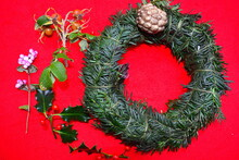 English Yew Tree Branches Twisted To Form The Traditional Christmas Evergreen Wreath Ring To Be Decorated With Natural Winter Foliage Including Rose Hips Red Berry Holly Gaultheria Pink Berries Shrub.