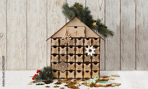 Fotomural Wooden house shaped advent calendar, Christmas cookies and festive decor on whit