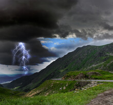 Dark Cloudy Sky With Lightning Striking Ground. Thunderstorm In Mountains