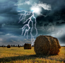 Picturesque Lightning Storm Over Field With Rolled Hay Bales