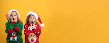 Kids In Christmas Sweaters And Santa Hats On Yellow Background, Space For Text
