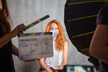 Operator Holding Clapperboard During The Production Of Short Film. Actress With Red Hair And Surgical Mask On Stage. Blur Effect On The Clapperboard And Monitors. Work In Times Of Coronavis, Covid-19.