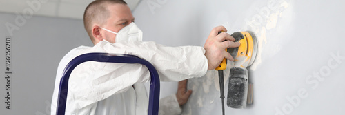 Fotografía Male builder in uniform cleans wall with putty