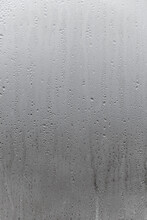 Natural Drops Of Water Flow Down The Glass, High Humidity In The Room, Condensation On The Glass Window. Neutral Colors. Vertical Photo Orientation