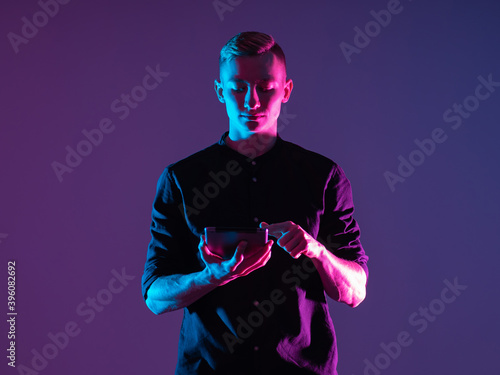 Obraz Man with a tablet on a purple background. It is illuminated by neon light. Concept - he uses a tablet application. Guy is using the app in the gadget. Student is using some kind of application - fototapety do salonu