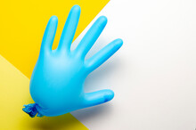 Blue Medical Glove Inflated On Yellow Back